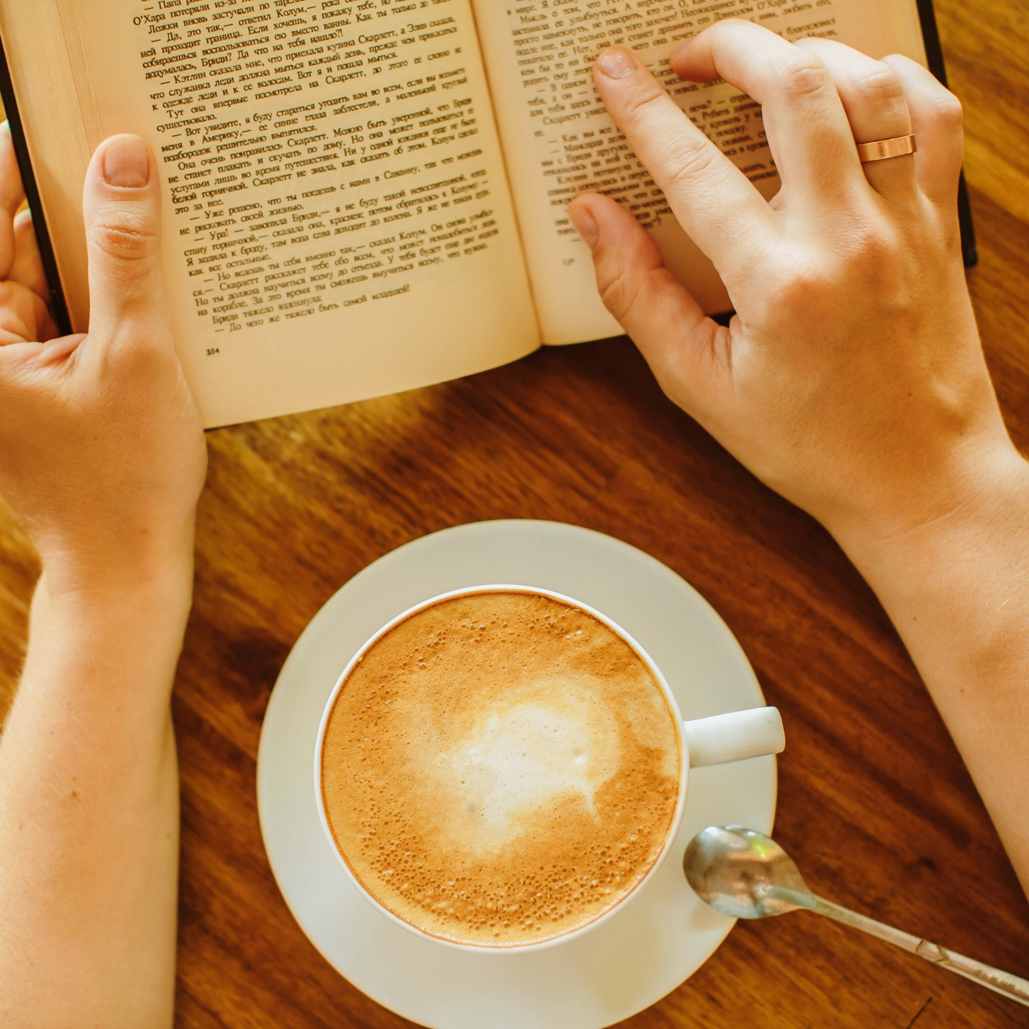 Woman hands, coffee and book on the table