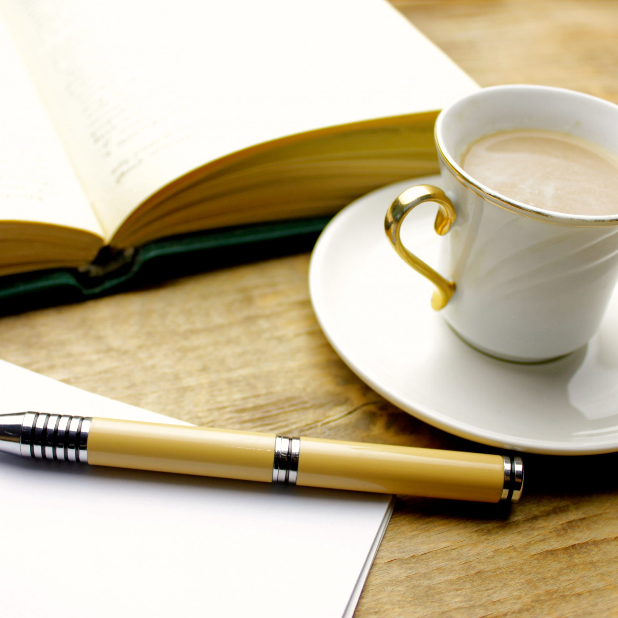 books, pens, open clean notebook with a cup of coffee